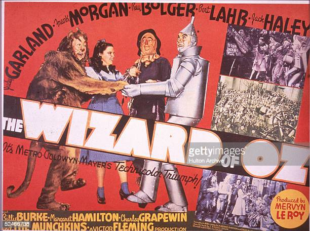 A lobby card from the film 'The Wizard Of Oz' shows an illustration of American actors Bert Lahr Judy Garland Ray Bolger and Jack Haley in costume as...