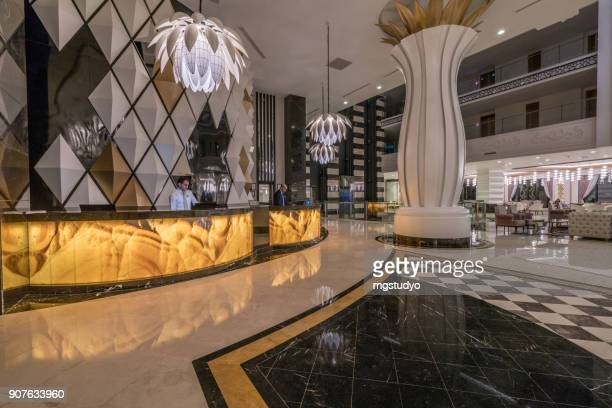lobby entrance with reception desk and lounge area - hotel stock pictures, royalty-free photos & images
