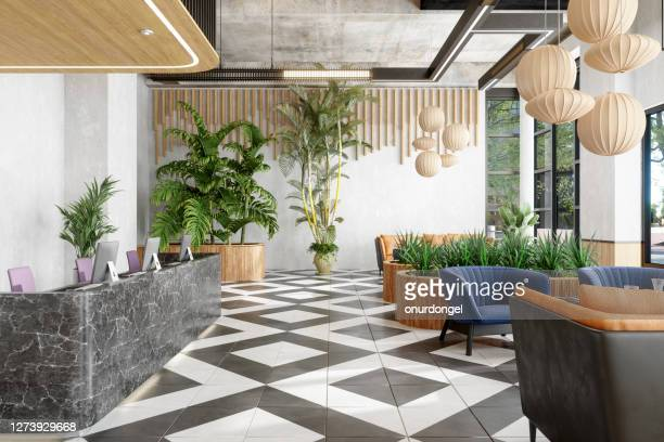 lobby with reception desk and lounge area with plants - luxury hotel stock pictures, royalty-free photos & images