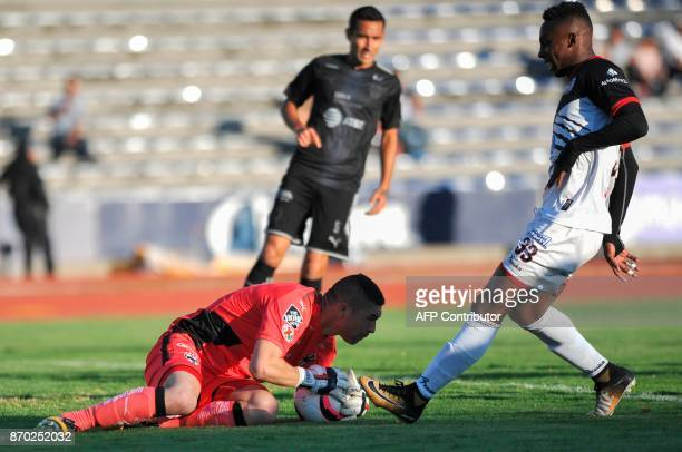 Lobos Buap's Julian Quinones vies for the ball with Monterrey goalkeeper Juan Carrizo during their 2017 Mexican Apertura Tournament football match at...