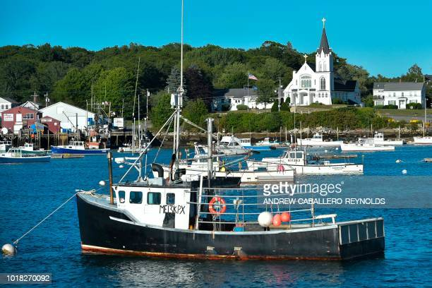 Lobster fishing boats are moored near a church in Boothbay Harbor Maine on August 10 2018