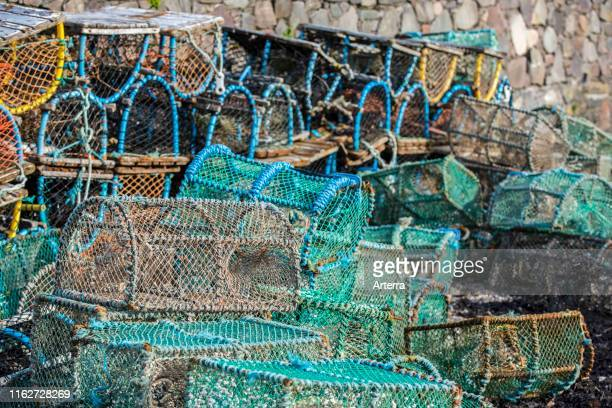 Lobster pots / prawn creels stacked against harbour wall in Plockton, Scottish Highlands, Scotland, UK.