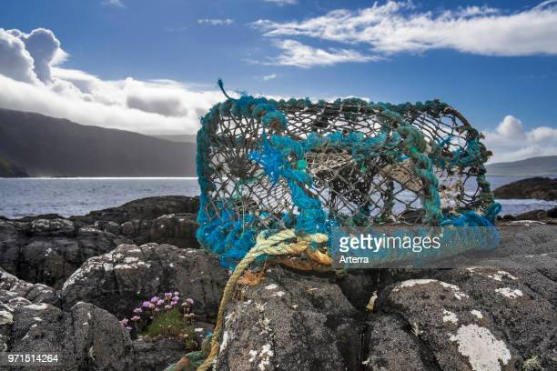 Lobster trap / lobster creel made of nondegradable plastic and nylon washed ashore on rocky beach in Scotland UK