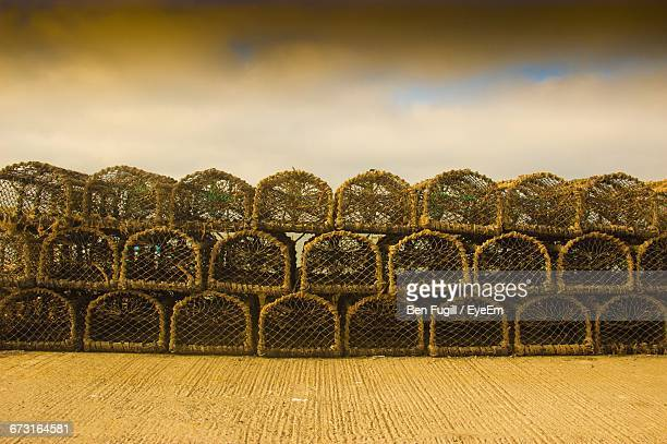lobster traps for sale on footpath against cloudy sky - モーペス ストックフォトと画像