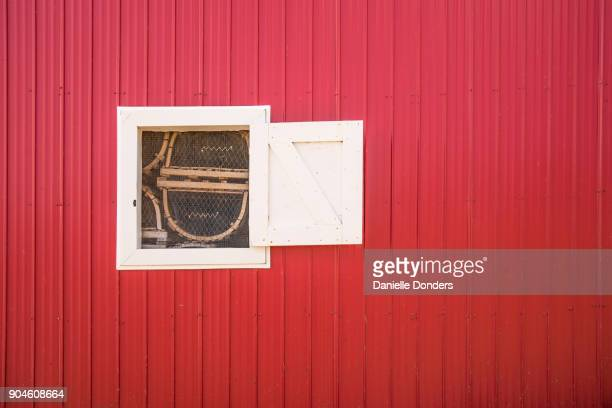 Lobster traps through a window on a red shack