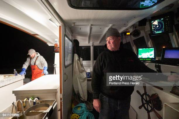 Lobsterman John Williams keeps a hand on the throttle of his lobster boat while sterman Zachary Carter prepares the boat early in Stonington before...