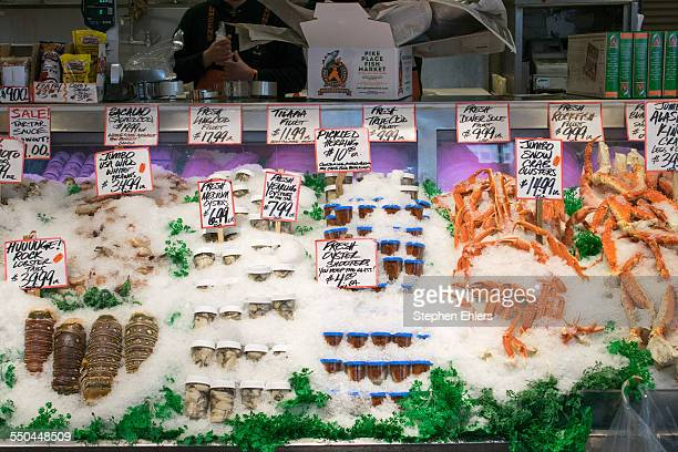 Lobsters crab legs oyster shooters and a variety of seafood for sale at a shop in Pike Place Market
