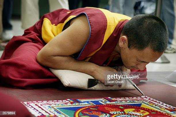 Lobzang Tuskhor a Tibetan monk from the Lhunpo Monastery in southern India helps to create a sand Mandela one piece of sand at a time at the Field...