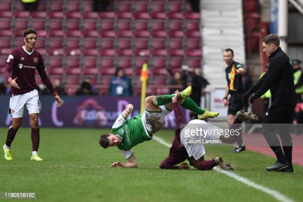 Loïc Damour of Heart of Midlothian FC takes out Lewis Stevenson of Hibernian FC during the Ladbrokes Premiership match between Hearts and Hibernian...