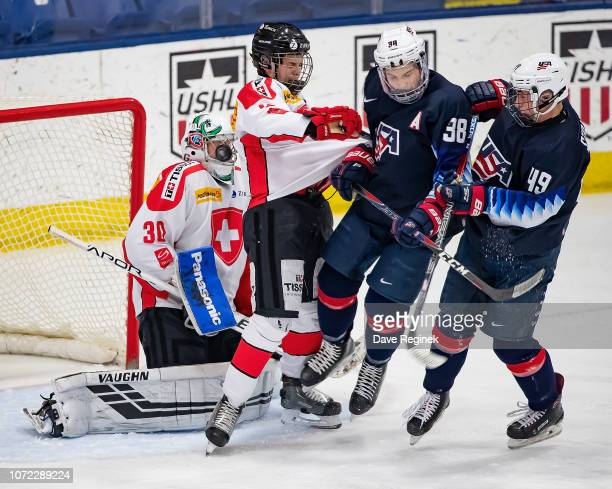 Loïc Galley of the Switzerland Nationals makes a save as teammate Giancarlo Chanton battles in front of the net with Landon Slaggert and Hunter...