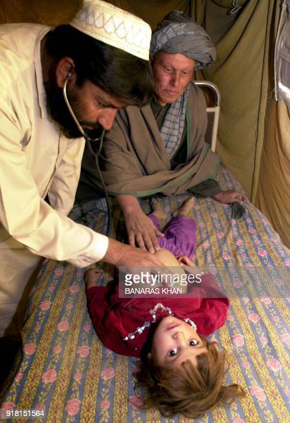 A local Afghan doctor checks up a child suffering from a cold and cough 16 December 2002 in the Afghan border town of Spin Boldak According to UNHCR...