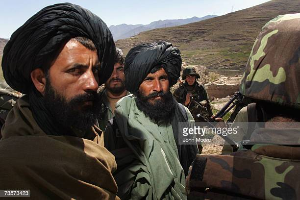 Local Afghan militia and Afghan Army soldiers consult March 14, 2007 in Kajaki, Helmand province, Afghanistan. Afghan troops, along with British...