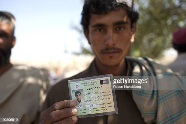 Local Afghan residents show their identity cards before entering a polling station to vote in the nationwide presidential election on August 20 2009...