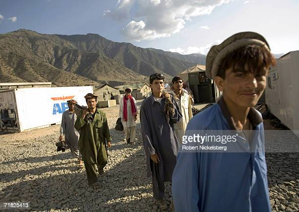 Local Afghan workers walk through the Forward Operation Base at the end of the day on August 30 in Naray Kunar eastern Afghanistan The 10th Mountain...