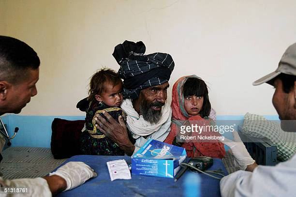Local Afghans in Wazakhwa sit in a medical clinic waiting to be treated by US Army medics from the 25th Infantry Division in south eastern Paktika...
