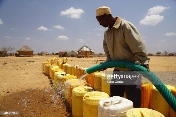 A local aid worker provides a 'Clean Water' delivery at the UN aid relief camp at Bandadero village near Moyale North Kenya Last week the Kenyan...