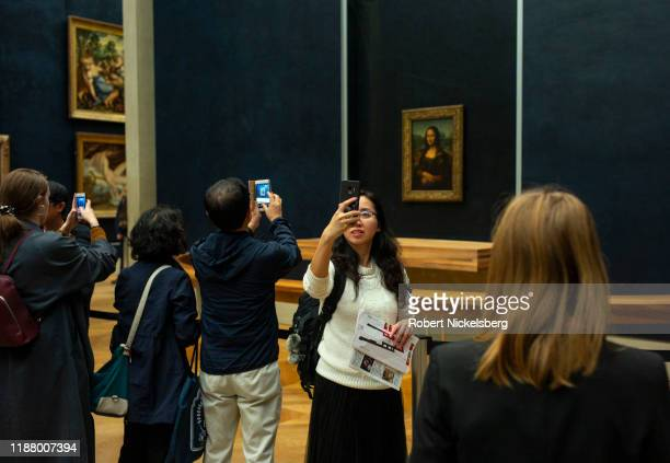 Local and foreign tourists stand in line to view and take pictures of the Mona Lisa painting by Leonardo da Vinci at the Louvre Museum in Paris...