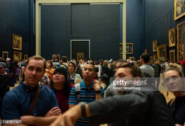 Local and foreign tourists stand in line to view the Mona Lisa painting by Leonardo da Vinci at the Louvre Museum in Paris France on November 6 2019...