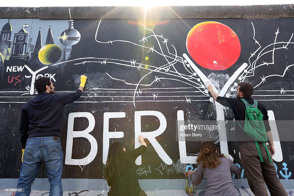 Local and tourist volunteers scrub graffiti from the East Side Gallery, the mural-covered longest remaining stretch of the original Berlin Wall, on April 27, 2014 in Berlin, Germany. The 8 mile (1.3 kilometer) section of the Wall, which runs along the natural former East-West border of the river Spree, features works by 118 artists from 21 countries, contains 106 murals and is regularly 'tagged' by visitors. According to the artist's group 'East Side Gallery e.V.s', the city is not properly maintaining the murals with the group taking it upon themselves to start the initiative, calling for volunteers and its own member artists to participate.
