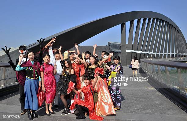 Local art groups pose for photos on opening day in front of the new National Palace Museum branch in the southern Taiwan city of Chiayi on December...
