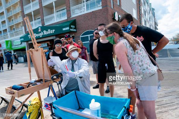 A local artist and onlookers wear masks on the boardwalk during the Memorial Day holiday weekend on May 23 2020 in Ocean City Maryland The beach...
