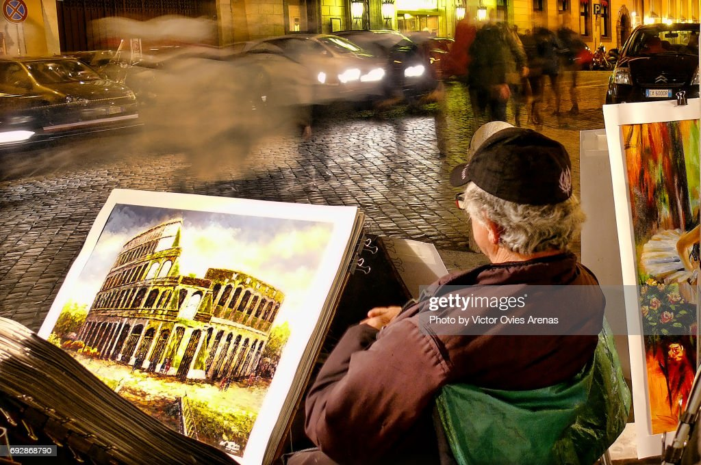 Local artist selling paintings at night in Rome, Italy : Foto de stock