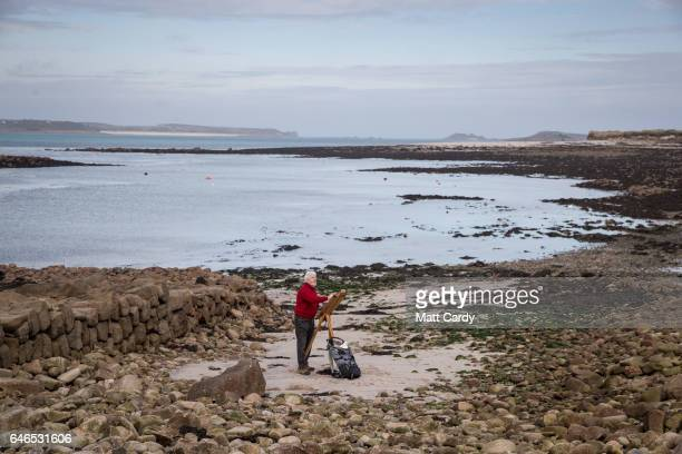 Local artist Steve Morris from the Glandore Gallery poses for a photograph as he paints on St Mary's on the Isles of Scilly on February 17 2017 in...