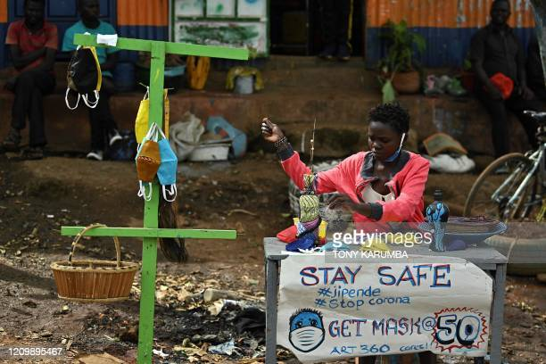 A local artists makes and sells face masks made from cloth in the Kibera slum Nairobi on April 14 2020 Kenya has so far cordoned off the capital and...
