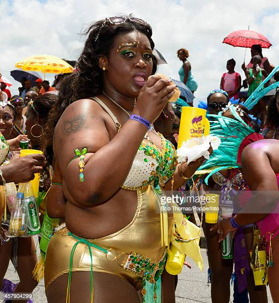 Local Bajan woman eating a hamburger during the Crop Over festival in Bridgetown Barbados 5th August 2013