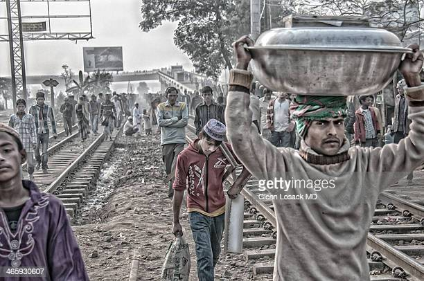 CONTENT] Local Bangladeshis walking on the railroad tracks toward the River Tuareg to celebrate IJTEMA the second largest HAJJ in ISLAM Man carrying...