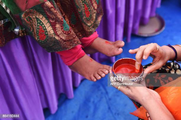 A local Bhartiya Janta Party leader prepares to touch the feet of the daughter of a labourer during the 'Kanya Poojan' ritual of the ongoing...