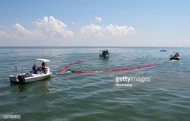 Local boaters pull an oil boom to test a porous polypropylene bag for the first time in the Gulf of Mexico near Dauphin Island Alabama US on Thursday...