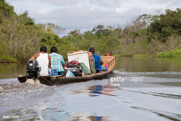 Local Bolivians moving furniture by canoe with outboard motor on the Yacuma River in the Pampas del Yacuma in Bolivia