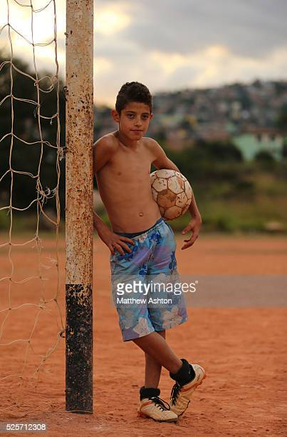 Local boy playing football standing next to a rustic goal net on a dust football pitch situated in between Rua Coronel Manuel Assuncao, Belo...