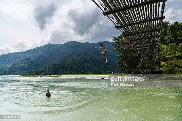 Local boys are jumping of a suspension bridge into the Harpan Khola river