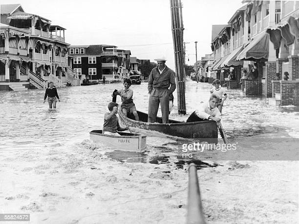 Local boys ferry a floodbound resident of Second Street in a canoe after high seas caused major flooding in the resort town of Ocean City New Jersey...