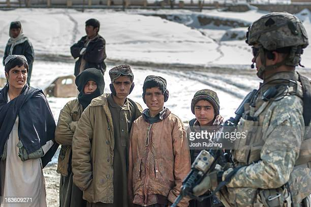 Local boys follow US soldiers from the 506th Infantry patrolling through the streets of the capital of Wardak Province. Maidan Shahr is where...