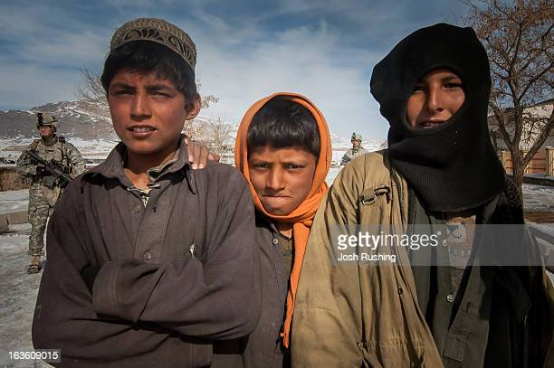 Local boys play in Maidan Shahr while US soldiers from the 506th Infantry patrol. Maidan Shahr is the capital of the Wardak Province, where President...