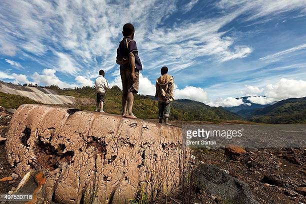 Local boys take in views of the dumpsites of the Porgera Joint Venture Gold Mine from an old Mining Truck tire Papua New Guinea Porgera Papua New...