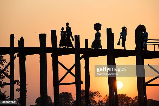 Local burmese people walking on famous U Bein bridge, made of teak wood, at sunset. A woman is carrying stuff on her head in the traditional way....
