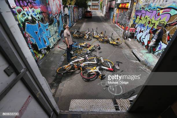 A local business owner looks on after Scott Wilson a ''bike wrangler'' hired by oBike dismantles an art installation that was stuck to a brick wall...