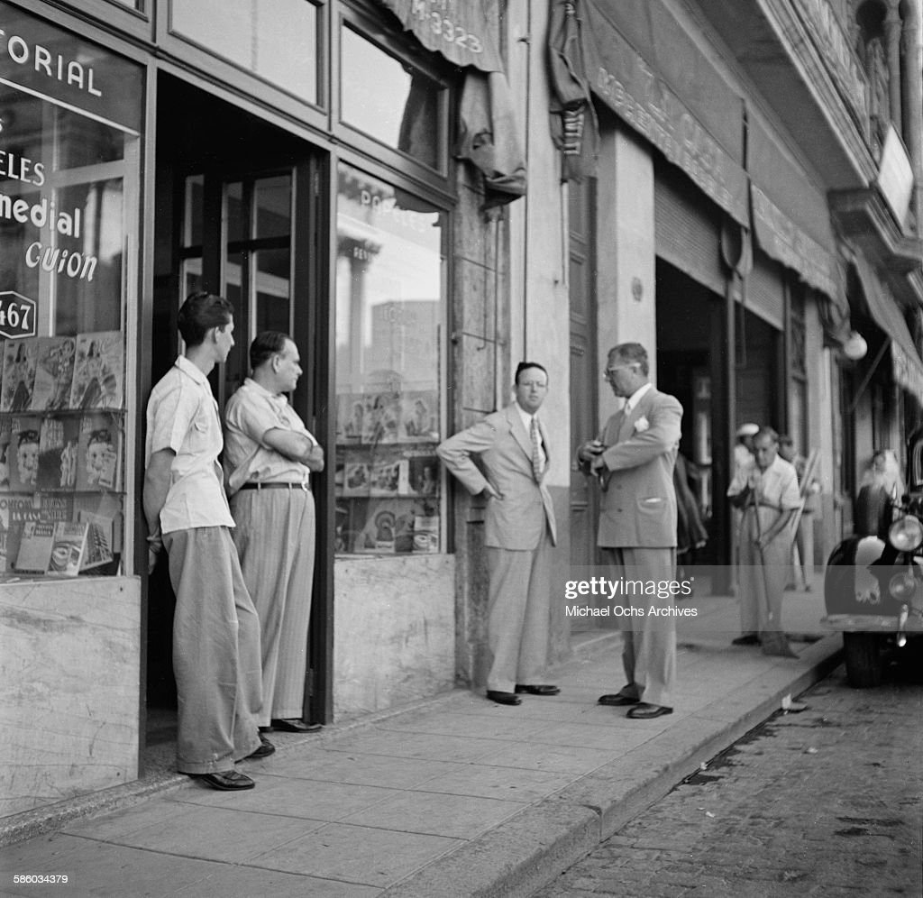 Local businessmen stand outside a shop in Havana, Cuba.