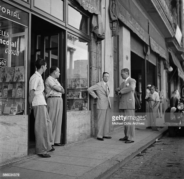 Local businessmen stand outside a shop in Havana Cuba