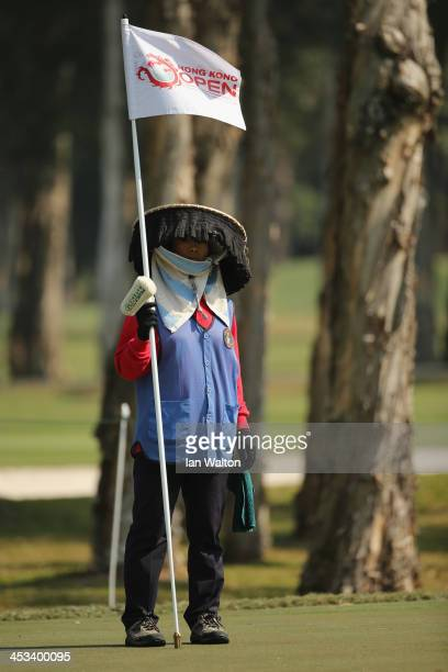 Local caddy stands with the pin flag during the Pro-Am at The Hong Kong Golf Club on December 4, 2013 in Hong Kong, Hong Kong.