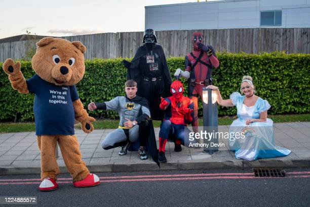 Local charity workers dressed as superheroes pose for a portrait after participating in the Clap for Carers at Tameside General Hospital in...