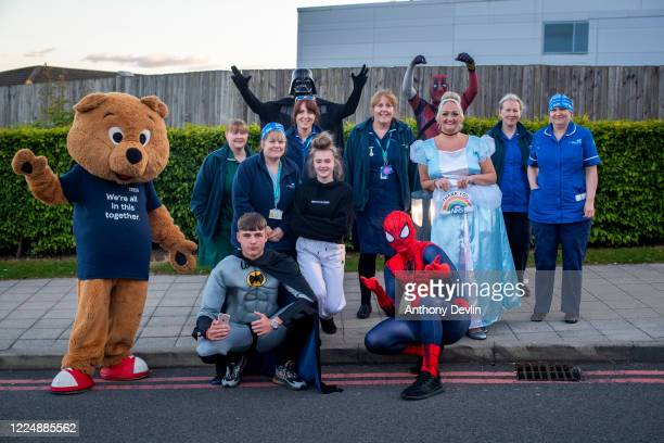 Local charity workers dressed as superheroes pose with NHS staff after participating in the Clap for Carers at Tameside General Hospital in...