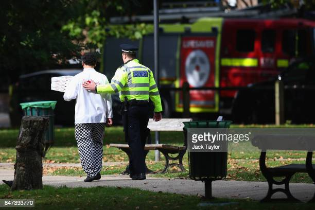 A local chef carrying free pizza is lead to Parsons Green station by a police officer on September 15 2017 in London England Several people have been...