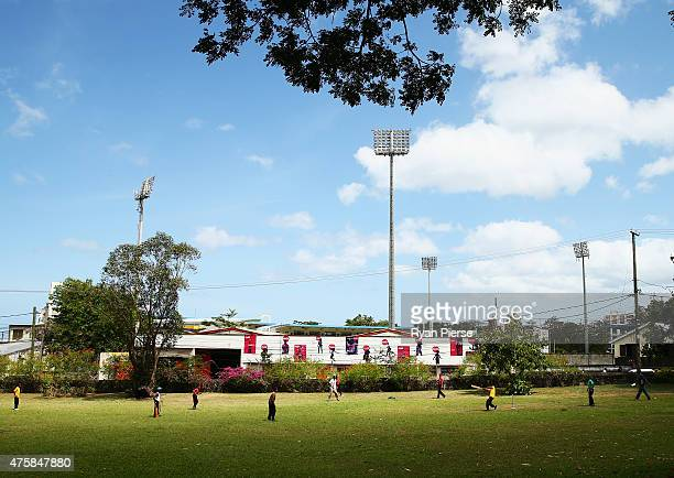 Local childen play cricket outside the stadium during day two of the First Test match between Australia and the West Indies at Windsor Park on June 4...