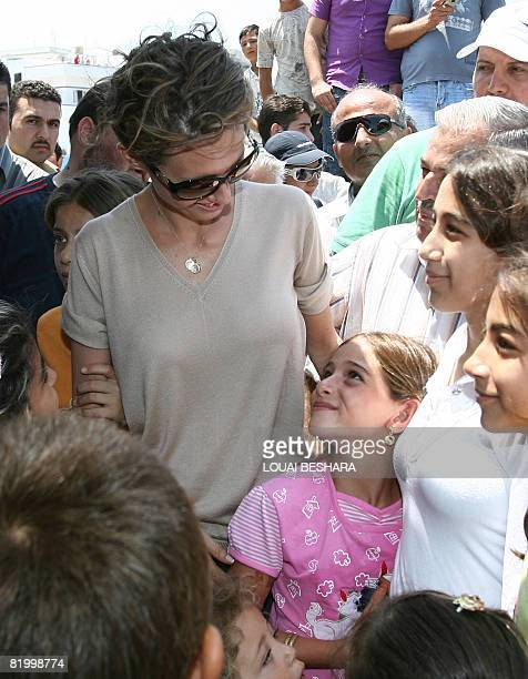 Local children gather around Syrian First Lady Asma alAssad during her visit to the harbour where a replica Phoenician ship is being built on the...