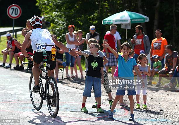 Local children give participants high fives as the cycle past during Ironman Klagenfurt on June 28 2015 in Klagenfurt Austria